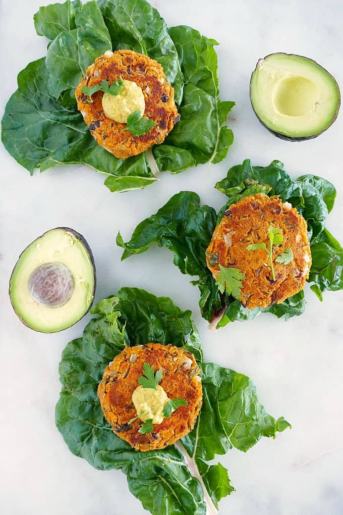 three sweet potato black bean burgers on top of lettuce leaves on a counter