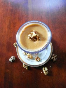 old photo of a sweet potato smoothie topped with walnuts on a wood table