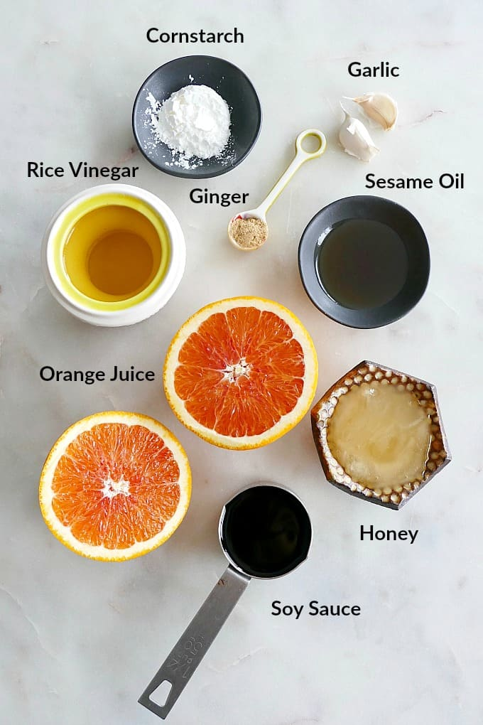 ingredients for orange sesame sauce with text overlay on a white counter