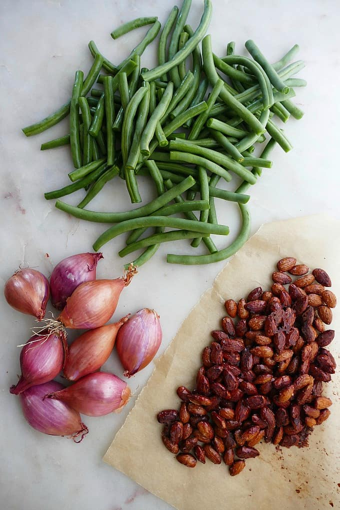 green beans, shallots, and a piece or parchment paper with maple roasted almonds