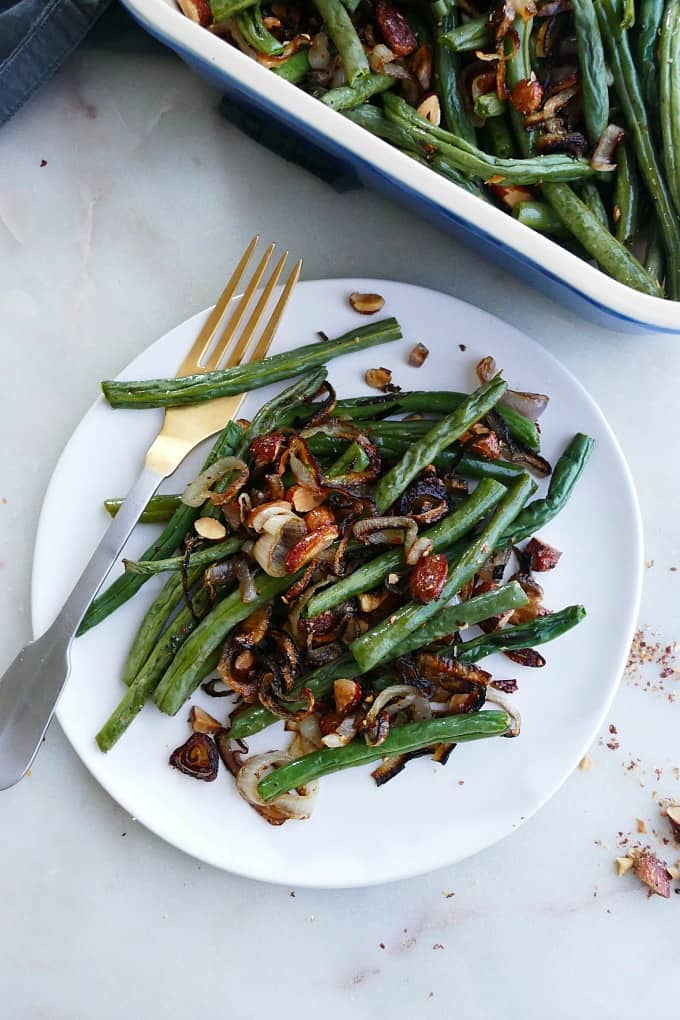 a serving of green bean casserole with almonds and shallots on a white plate