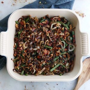green bean casserole made with maple almonds and crispy shallots in a square baking dish