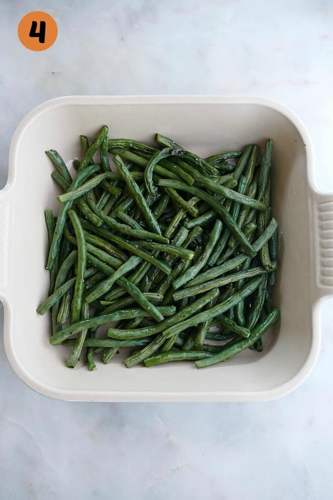 roasted green beans in a white square serving dish on a white counter