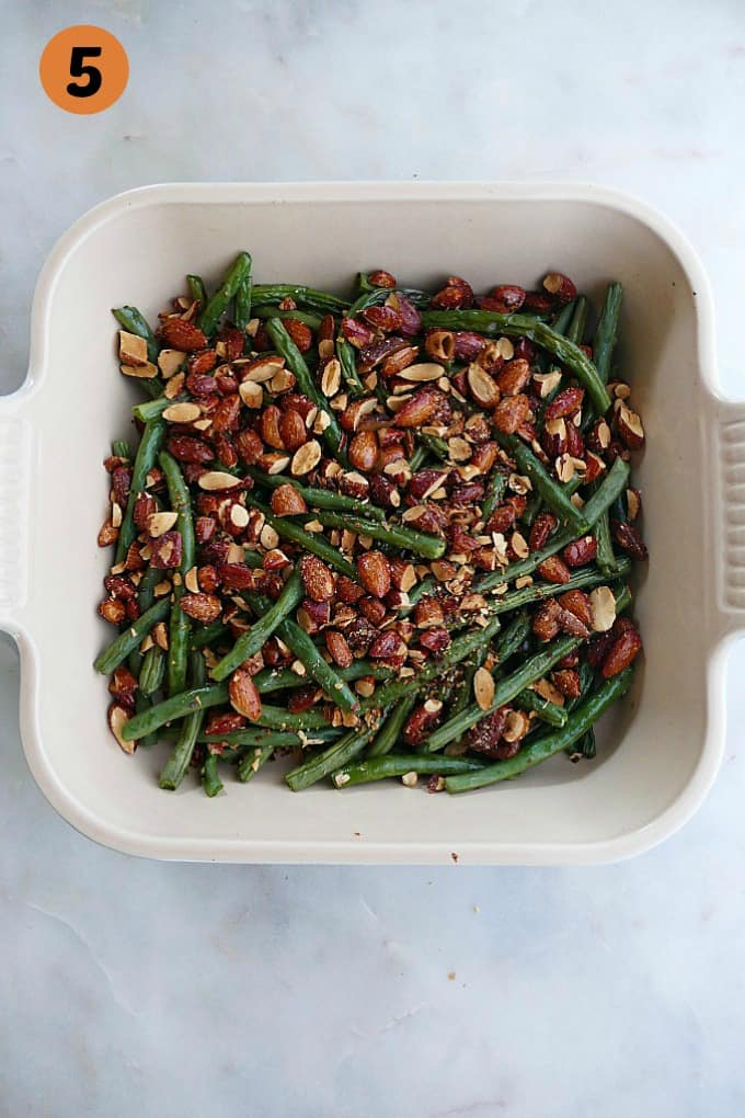 roasted green beans topped with chopped maple almonds in a square dish