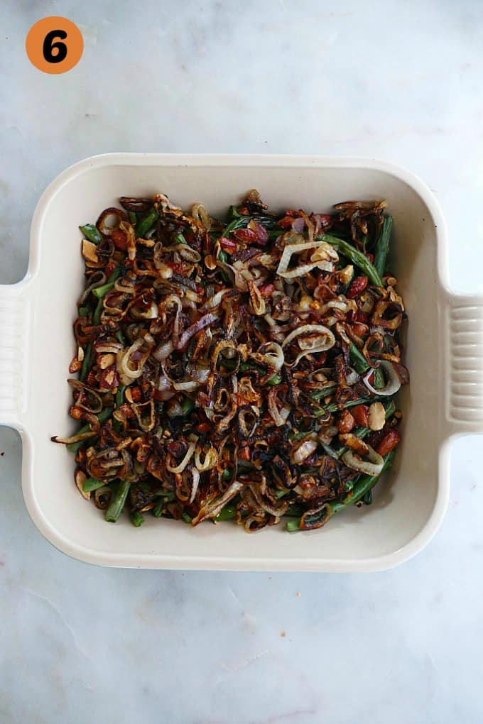 green bean casserole with almonds and crispy shallots in a square baking dish on a white counter