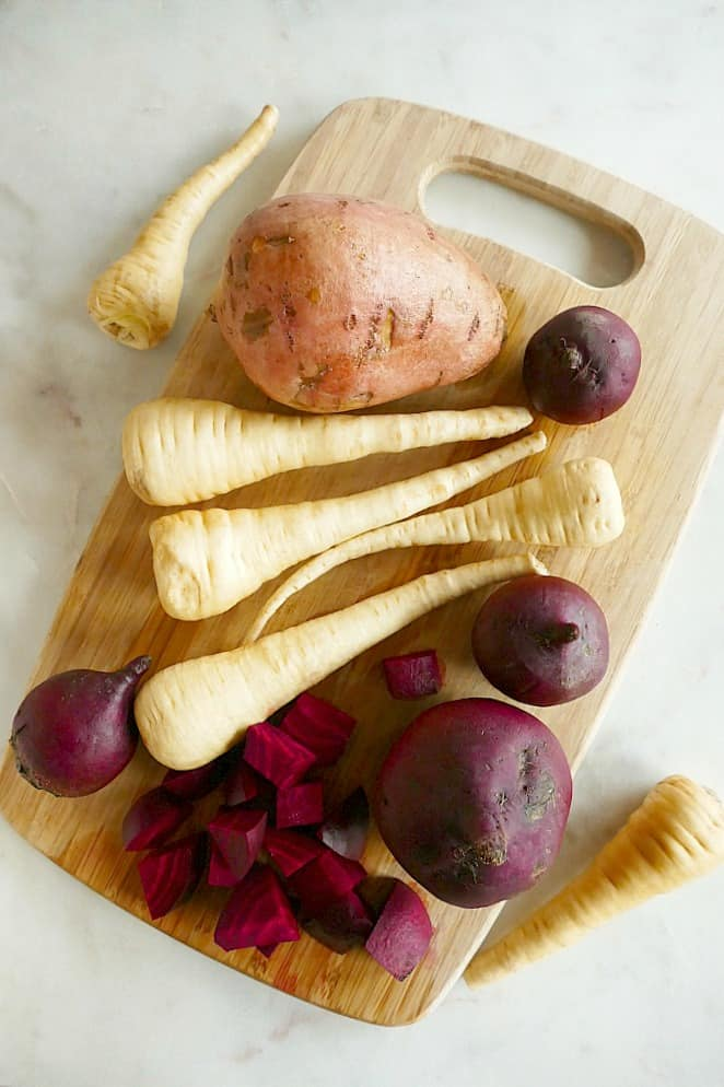 a bamboo cutting board with parsnips, beets, and a sweet potato on top