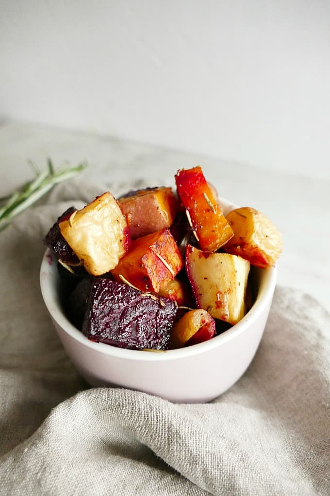 close-up shot of savory roasted root vegetables in a small pink bowl on gray napkin