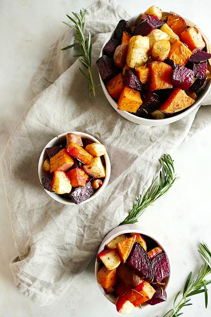 three bowls of savory roasted root veggies on a gray napkin with rosemary sprigs