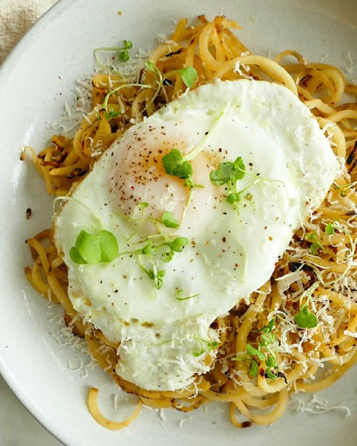 square image of rutabaga noodles topped with a fried egg in a dish