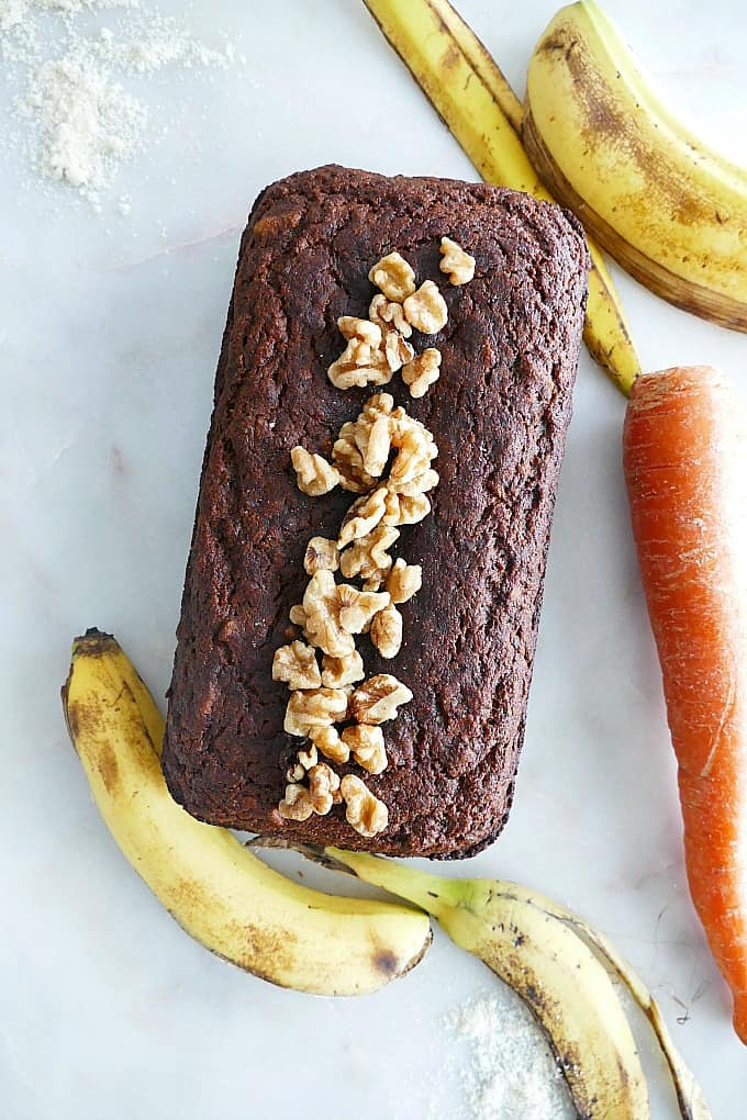 a loaf carrot banana bread topped with walnuts with bananas and carrots around it