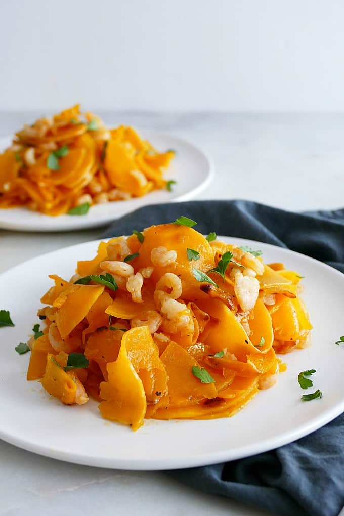 side angle of Butternut Squash Noodles and Shrimp on a white plate on a blue napkin