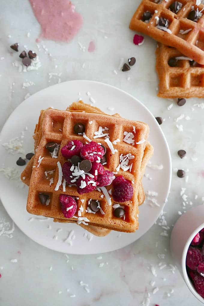 close up of a stack of pink waffles with raspberries and chocolate chips