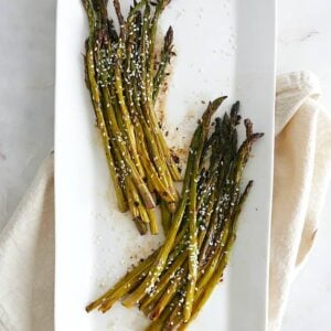 roasted sesame asparagus separated into two bunches on a white serving platter