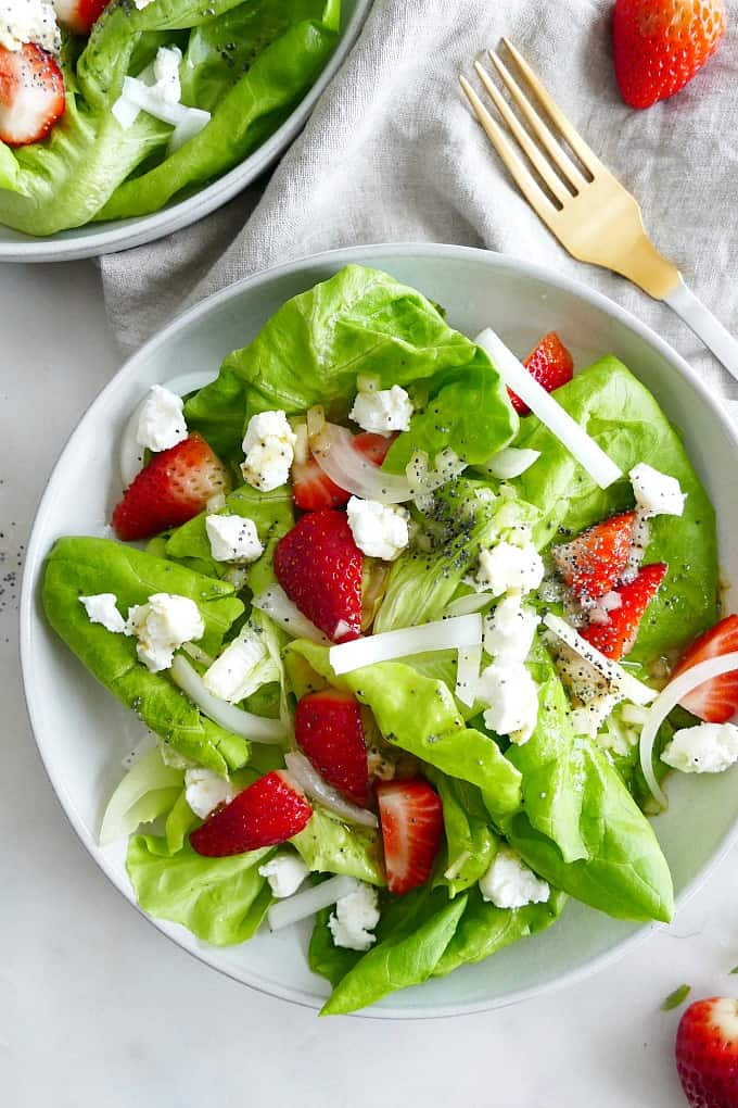 Butter Lettuce Strawberry Salad with goat cheese on a white plate on a counter