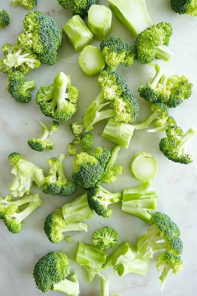 broccoli florets and stalks scattered across a white countertop