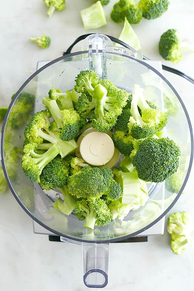 broccoli florets in a cusinart food processor on a white countertop