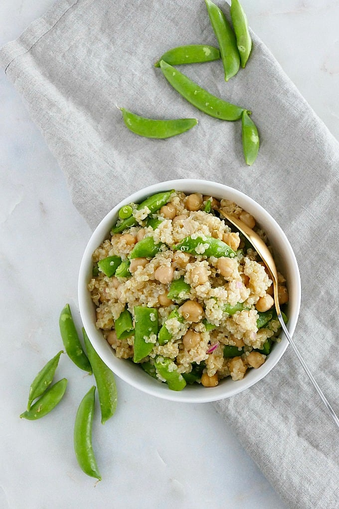 bowl of sugar snap pea quinoa salad on a napkin next to snap peas