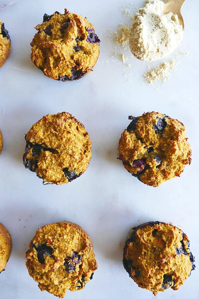 5 blueberry muffins on a counter next to a spoonful of milled flaxseed
