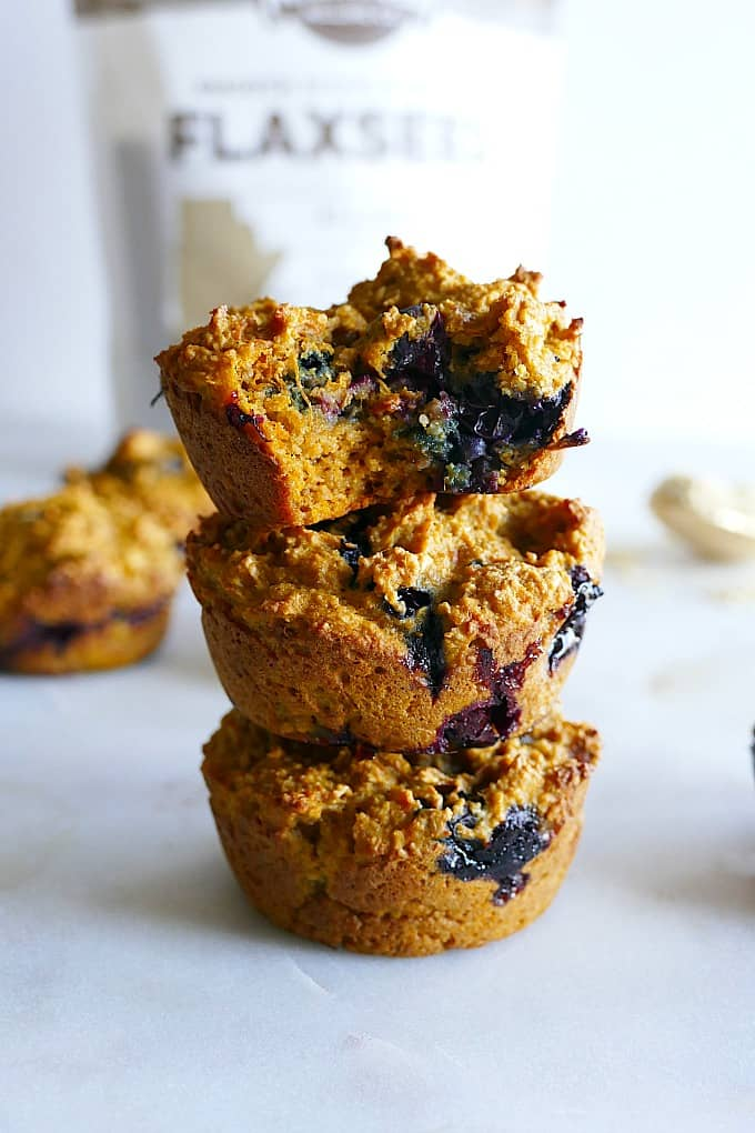 three sweet potato blueberry muffins stacked on top of each other on a counter