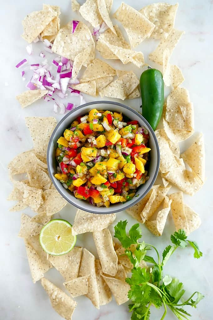 bowl of pepper mango salsa surrounded by ingredients and tortilla chips on a counter