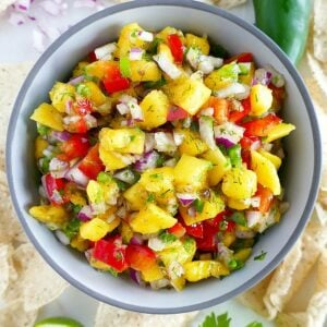 fresh mango salsa in a serving bowl surrounded by ingredients on a counter
