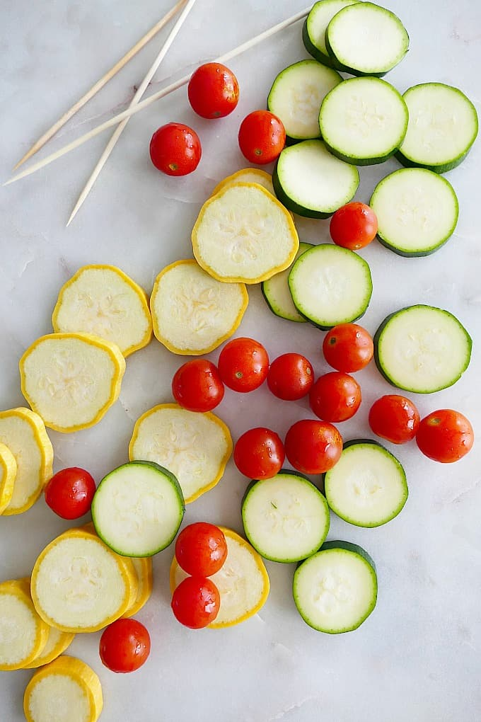 sliced yellow squash and zucchini with cherry tomatoes and skewers on a counter