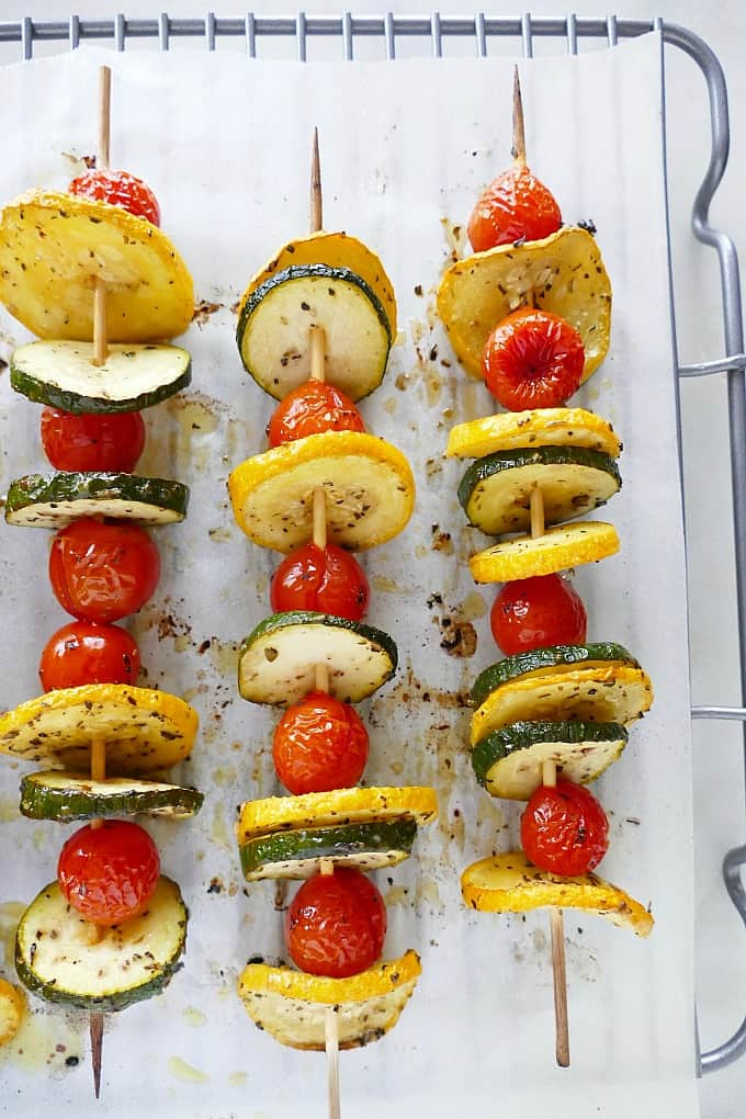 three kabobs with cherry tomatoes and summer squash slices on a cooling rack