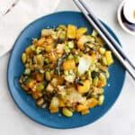 bok choy mango stir fry on a serving plate with chopsticks on the edge