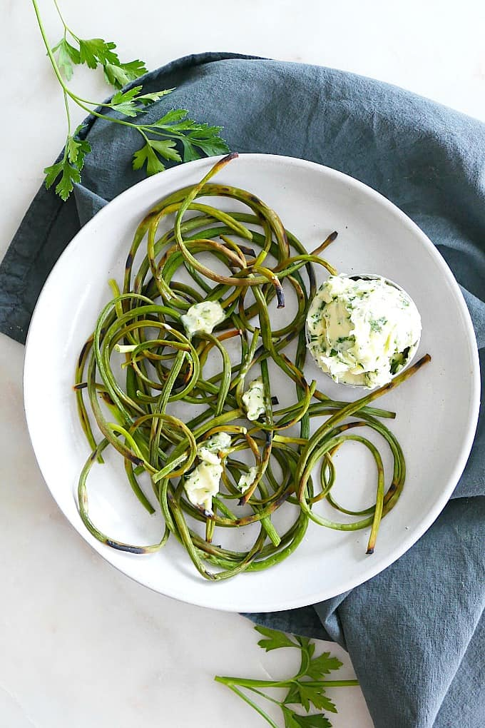 charred garlic scapes on a plate with a bowl of parsley butter