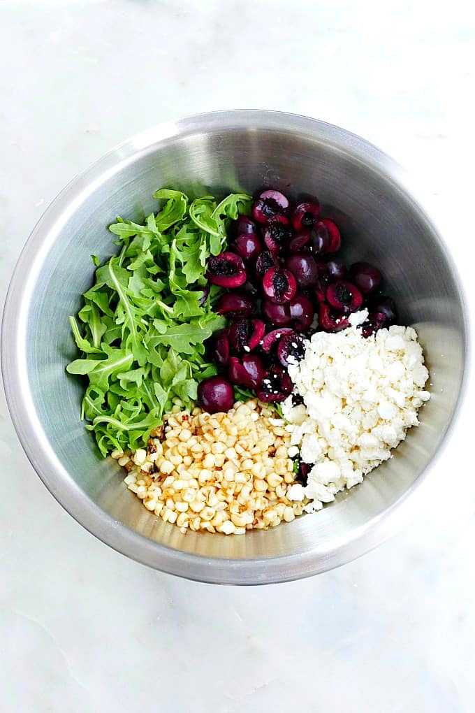 arugula, cherries, corn kernels, and feta cheese in mixing bowl on a counter