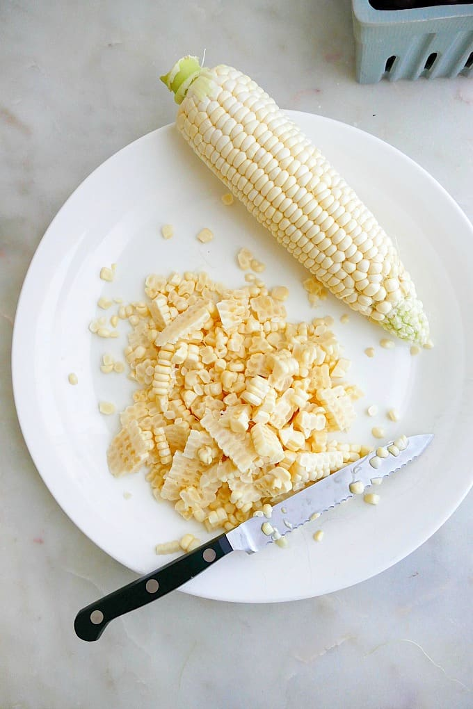 corn kernels next to a cob and a serrated knife on a white plate