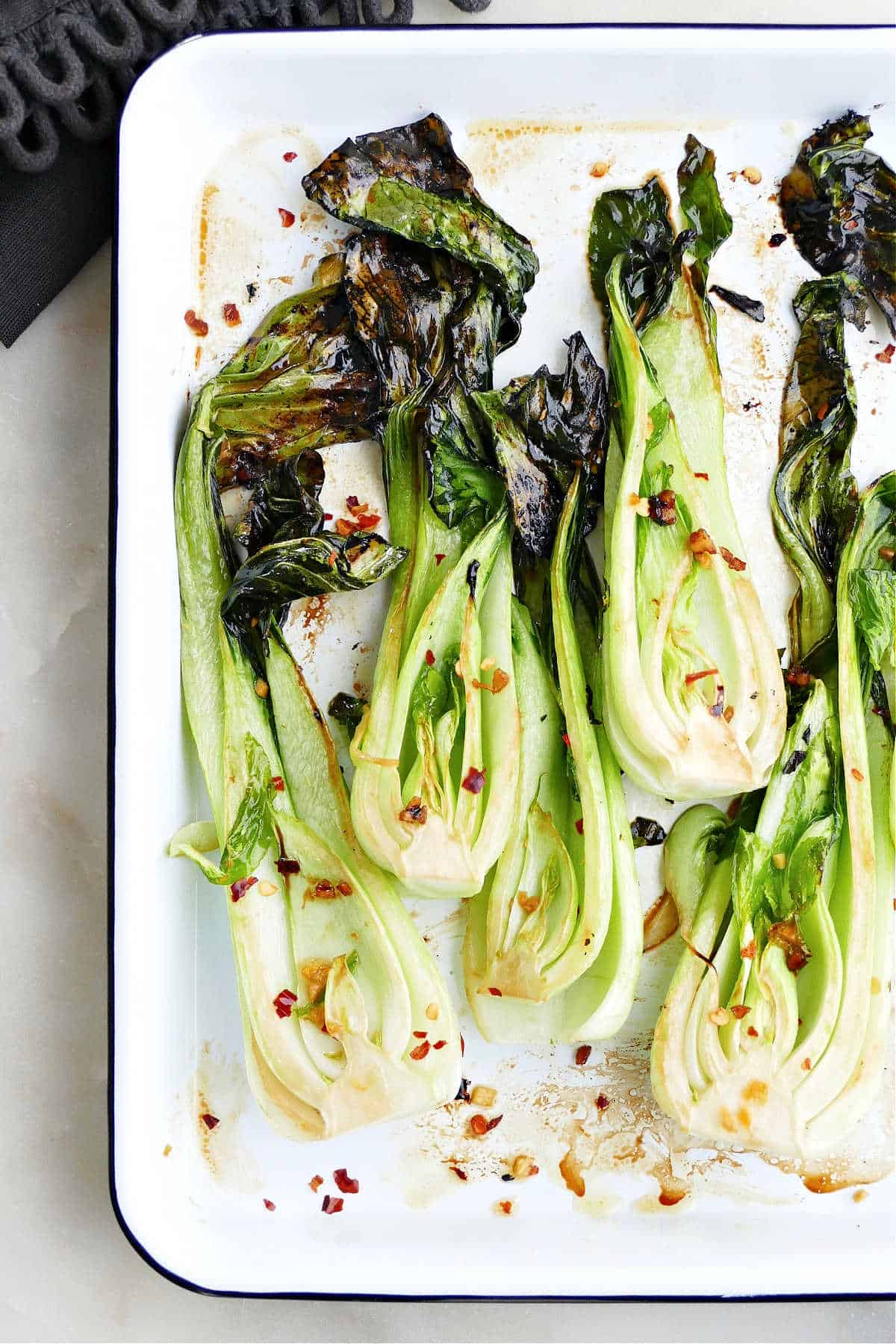 overhead image of roasted bok choy on a serving tray on a counter