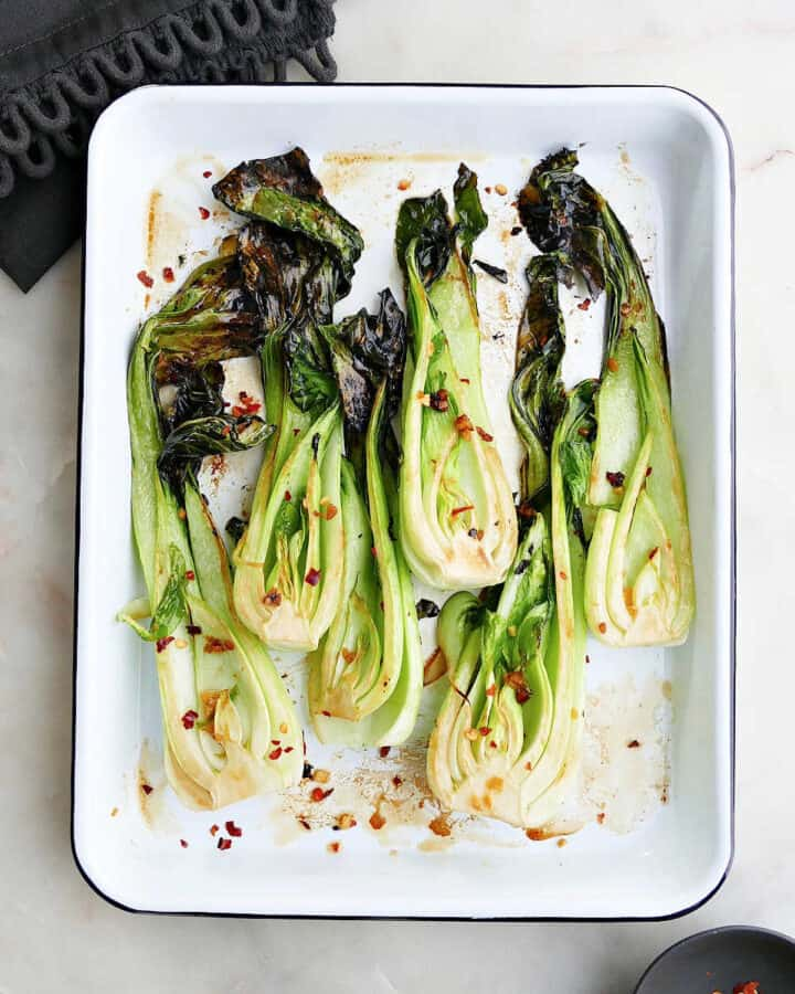 square image of roasted bok choy on a rectangular serving tray
