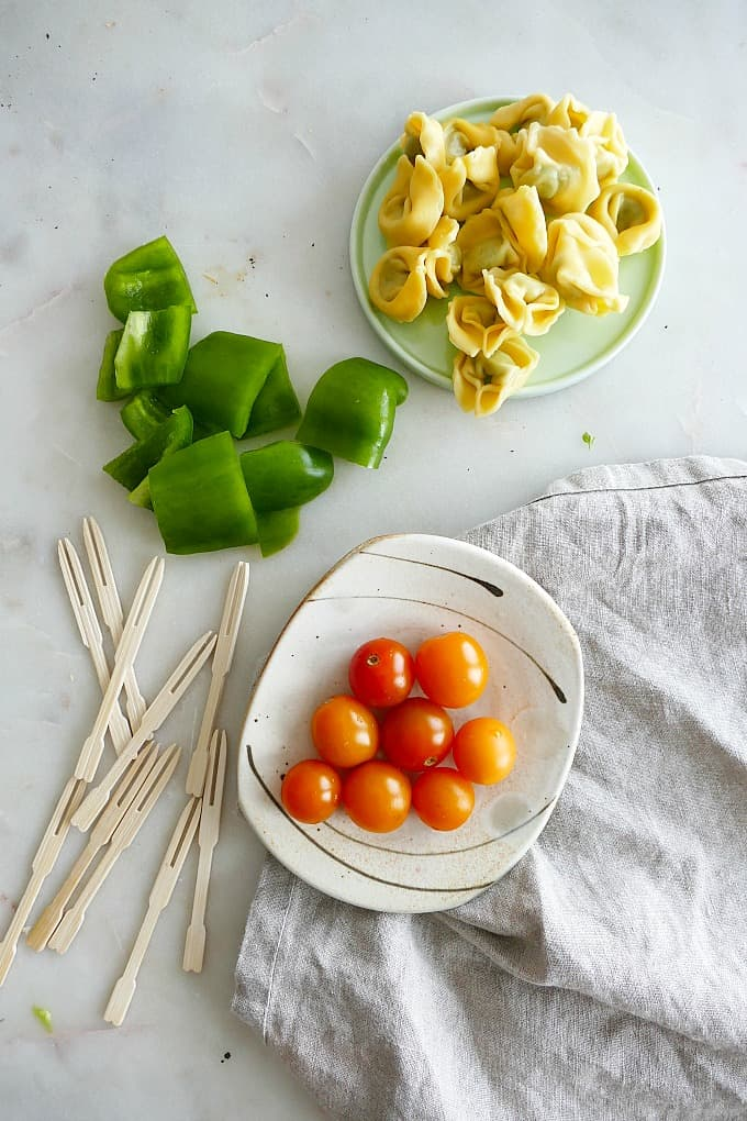 cooked tortellini, chopped bell pepper, cherry tomatoes, and toothpicks on a counter