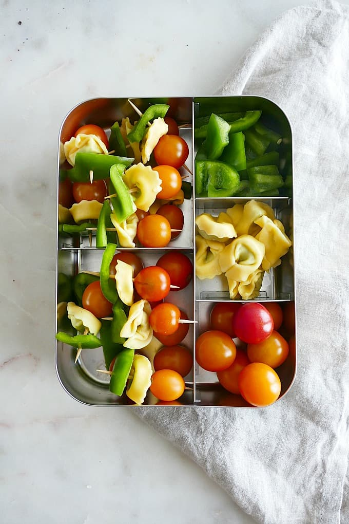 metal lunchbox filled with compartments of peppers, tomatoes, tortellini and finished skewers