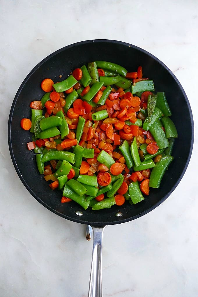 carrots, bell peppers, and snap peas in a black skillet on a white counter
