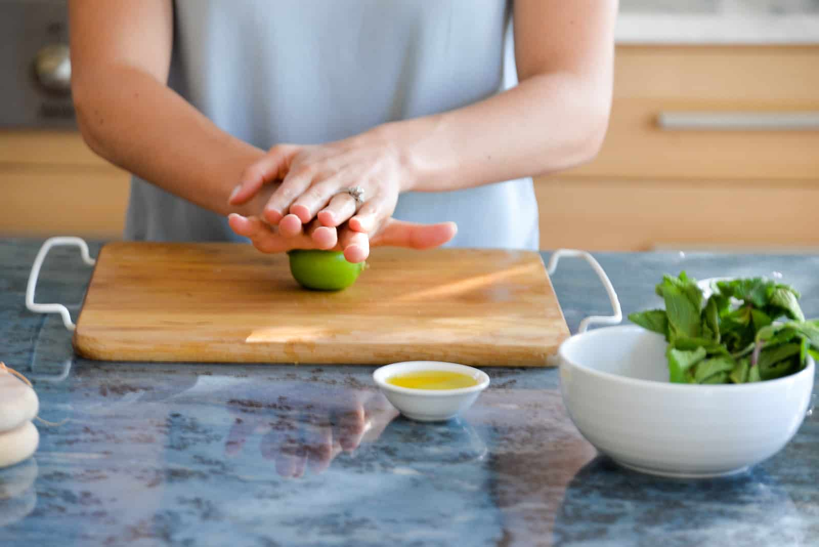 two hands of a woman rolling a lime on a bamboo cutting board