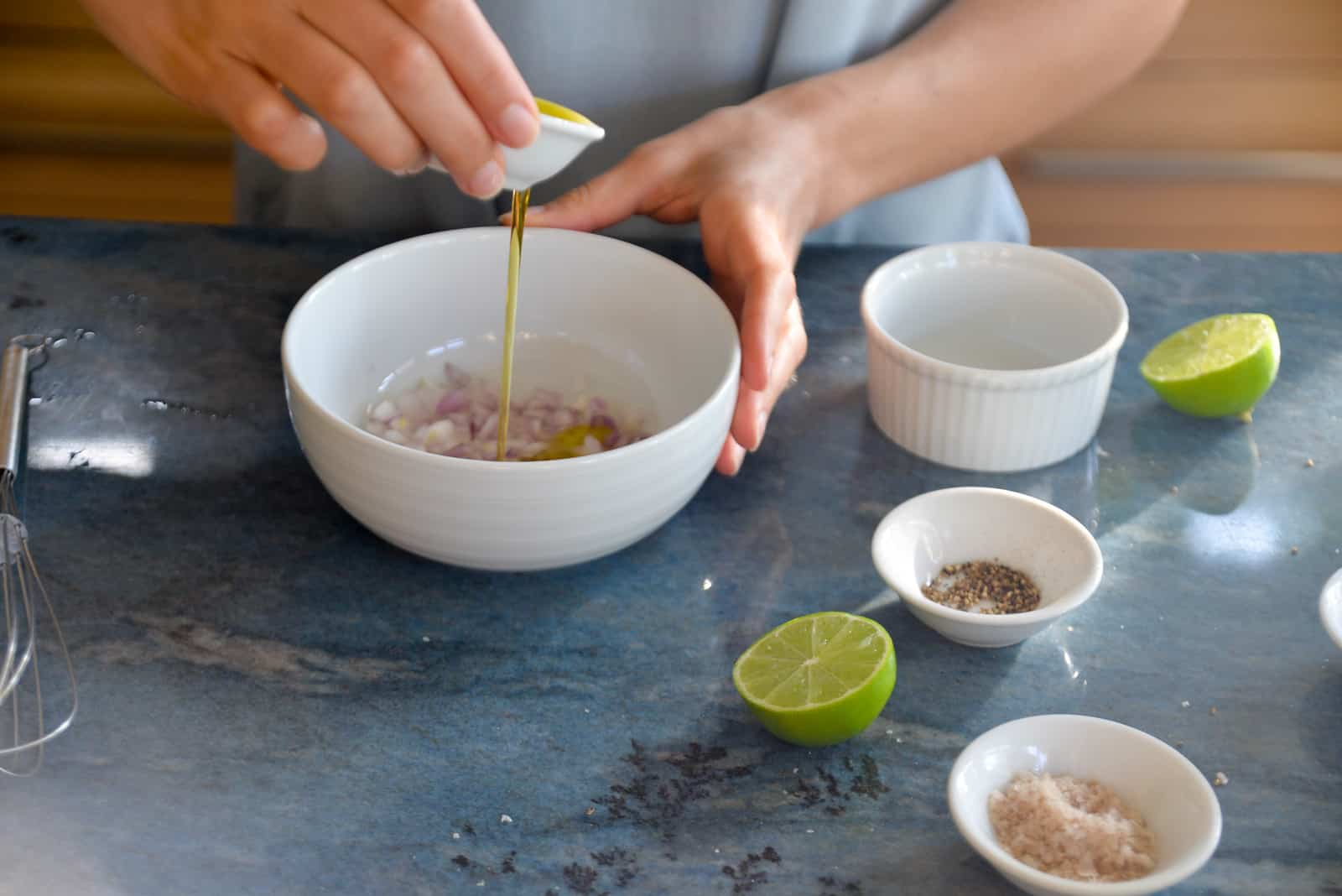 woman's hand drizzling olive oil into a white bowl with other ingredients