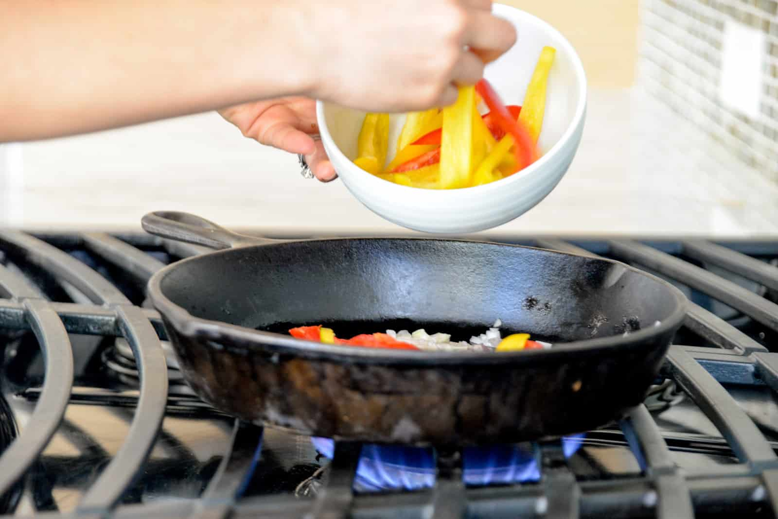 woman's hand dropping sliced bell peppers into a cast iron skillet over a range