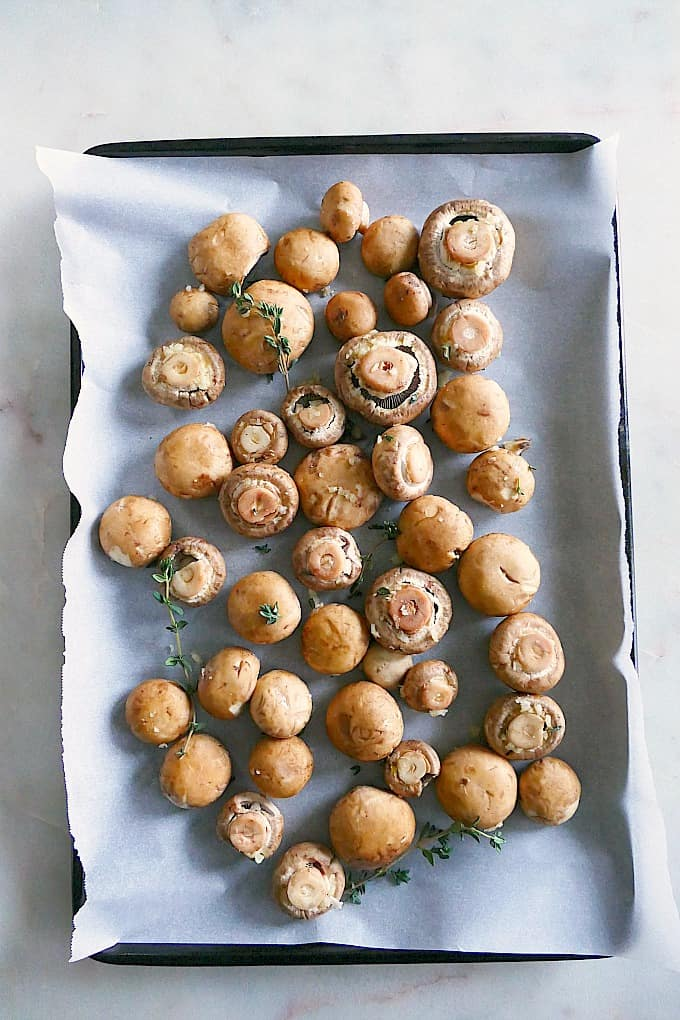 Garlic Thyme Roasted Mushrooms spread out on a baking sheet before baking