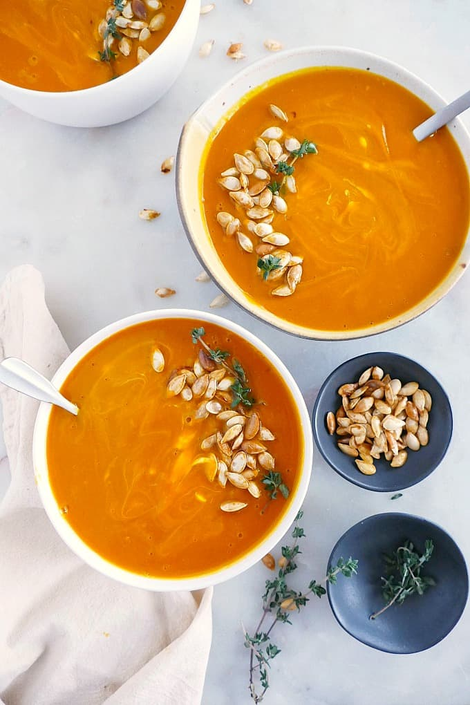 two bowls of soup topped with pumpkin seeds and thyme on a counter