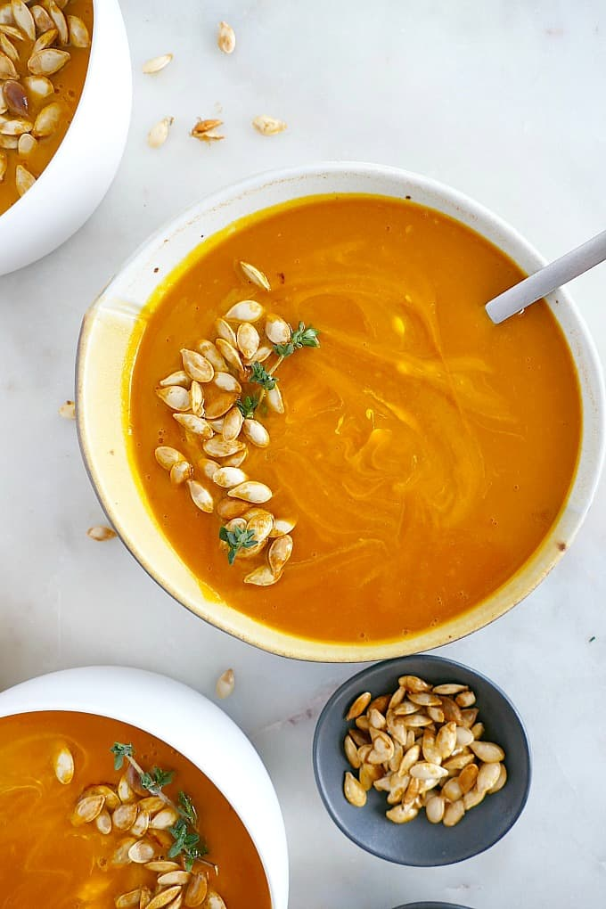 bowl of orange Kabocha Squash Soup topped with pumpkin seeds and fresh thyme
