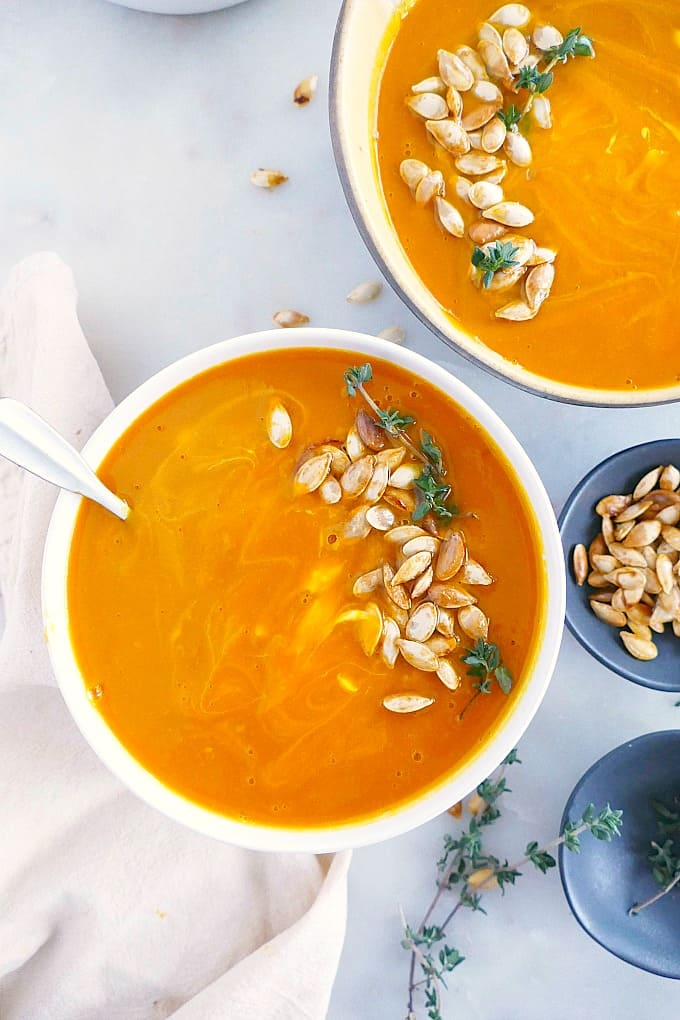 bowl of kabocha squash soup topped with pumpkin seeds and thyme on a counter