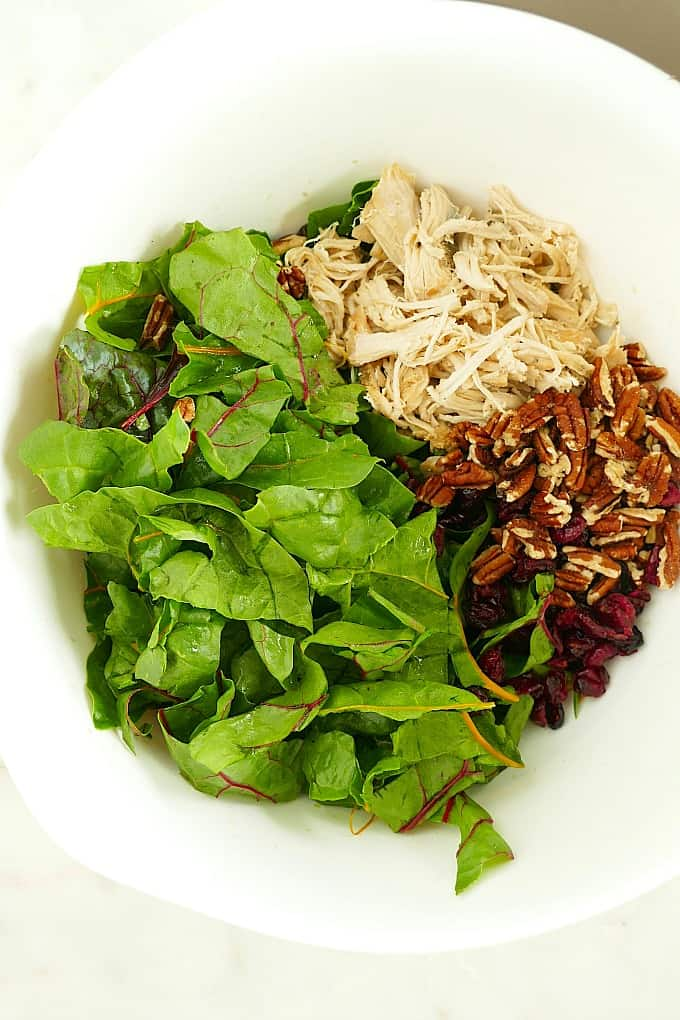 torn swiss chard, shredded turkey, pecans, and dried cranberries in a white mixing bowl