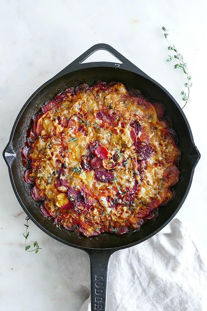 Turnip and Beet Gratin in a black cast iron skillet on a white countertop