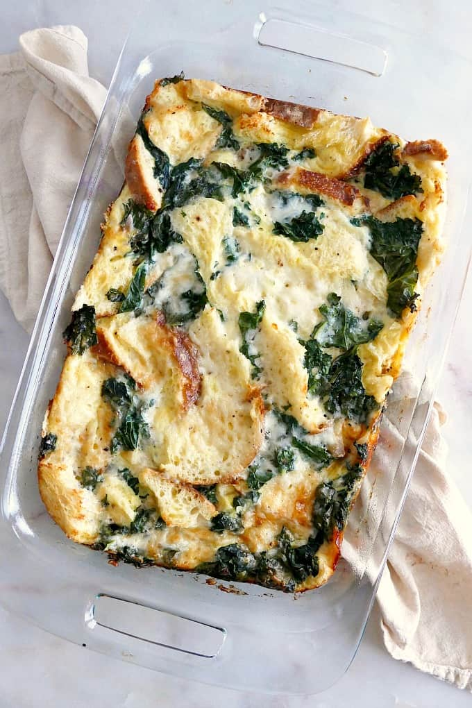 Sourdough Breakfast Strata with Kale in a glass pyrex on a yellow napkin