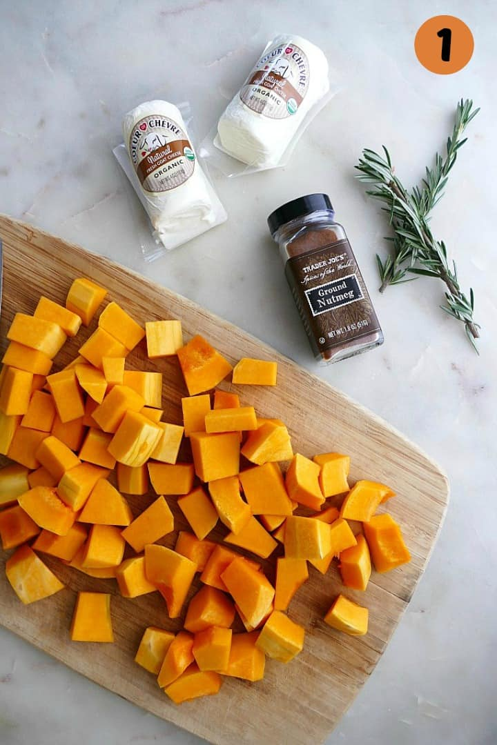 butternut squash on a cutting board next to nutmeg, rosemary, and goat cheese