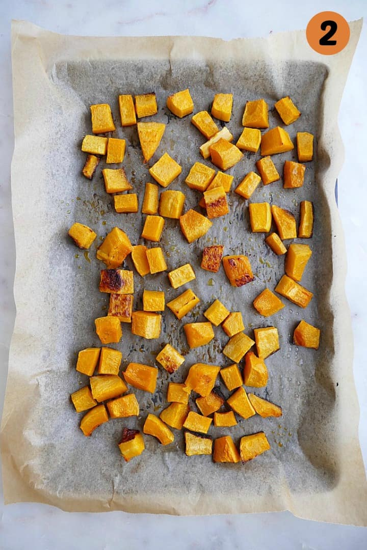 roasted butternut squash cubes on a baking sheet lined with parchment paper