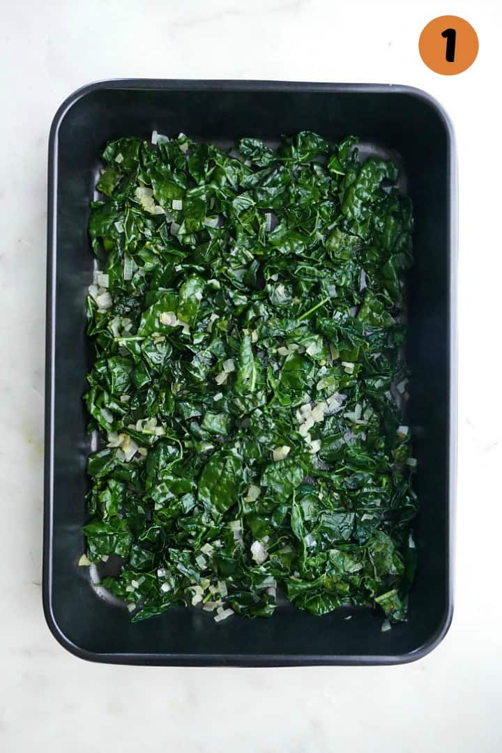 sauteed kale and shallots in a black 9x13 baking dish on a counter
