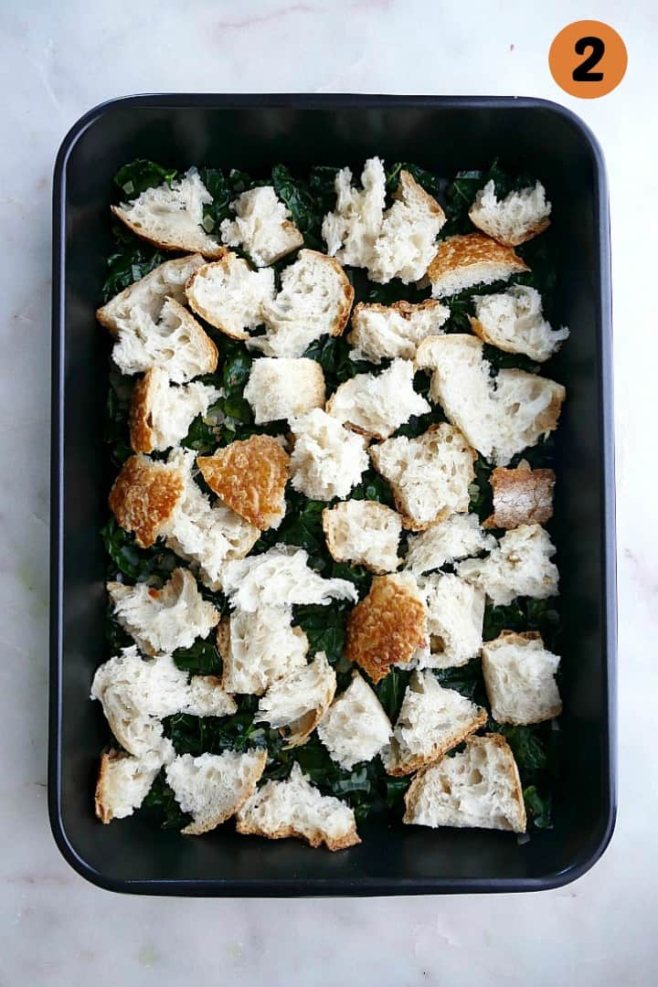 kale and shallots covered with sourdough bread cubes in a black 9x13 baking dish
